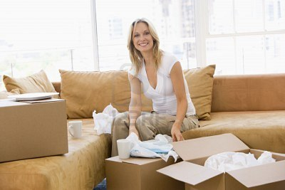 3486201-woman-unpacking-boxes-in-new-home-smiling